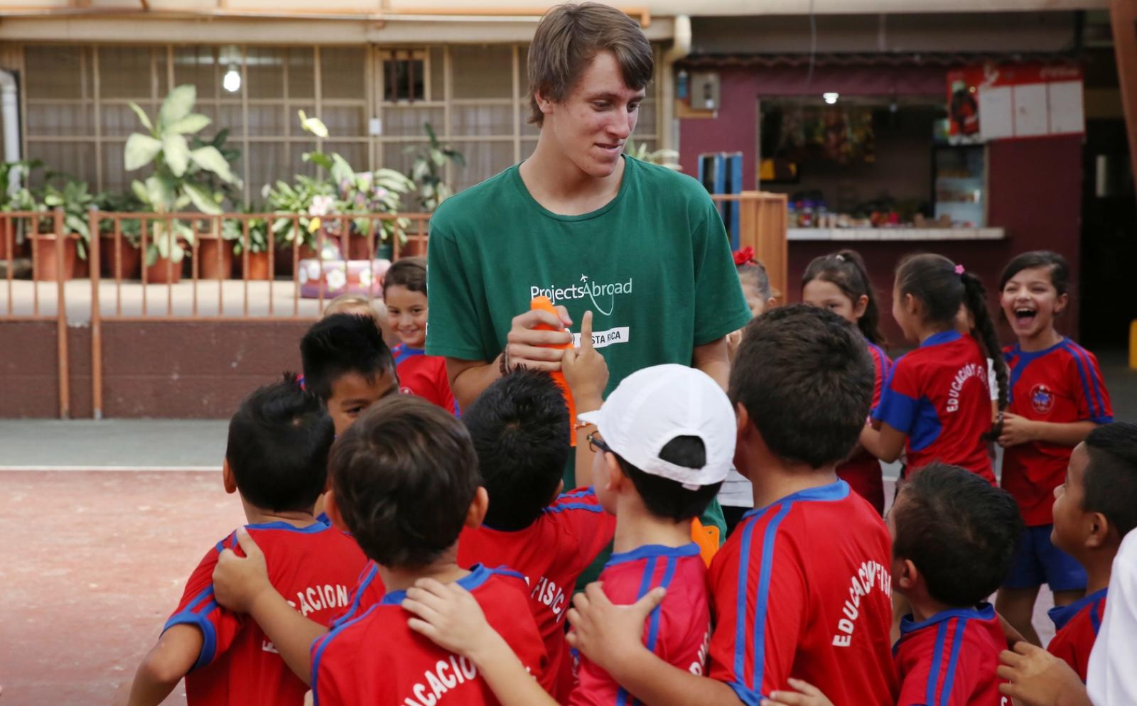 Children in Costa Rica around a Projects Abroad volunteer during a sport practice